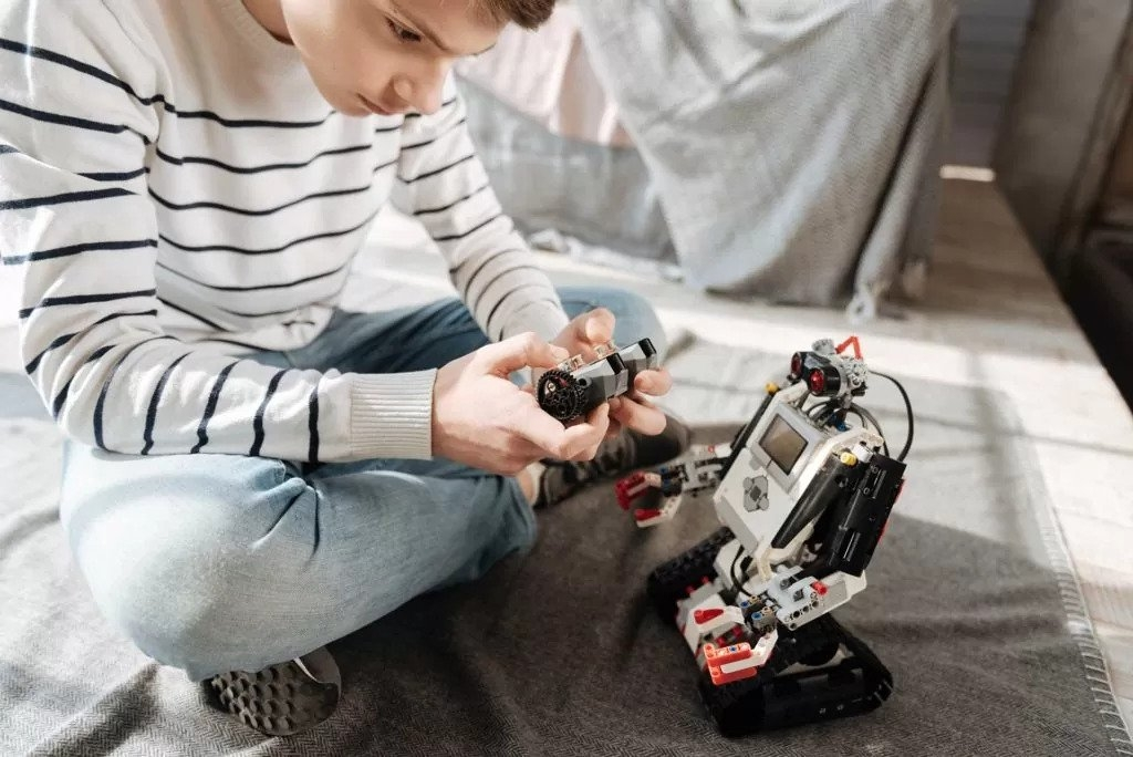 Boy plays with a robot toy that has a voice over