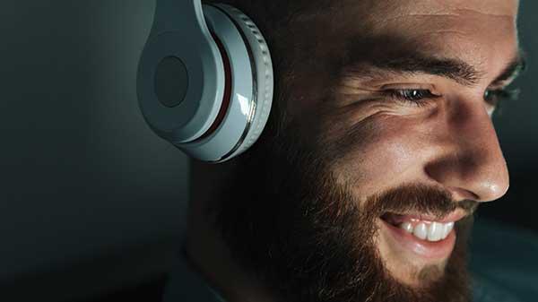Man smiling listening to an audio drama through headphones.
