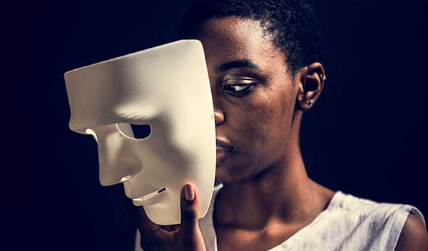 A black woman removes mask with intense expression.