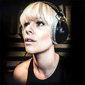 Headshot of Voice Coach Elizabeth Jobling wearing headphones