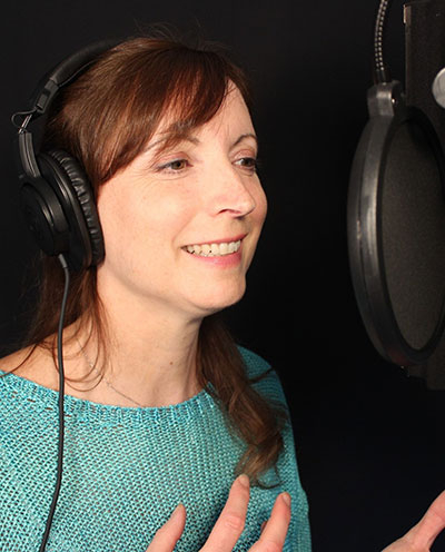 Voice artist reading a good voice-over script in studio boothe.